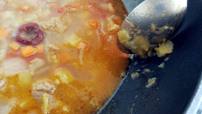 西红柿土豆炖牛肉,用勺底将部分土豆丁碾成泥,混在汤中