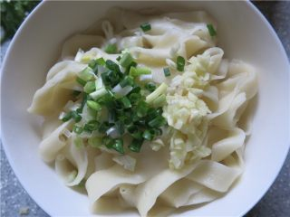 教你做一碗销魂的油泼面,开锅后煮大概1分钟左右,捞起面片看似透明就煮熟了,捞入大碗内,在面上面放入葱和蒜碎