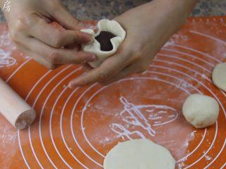 豆沙包,将豆沙馅置于面皮中间,拇指固定住一端,食指跟中指不停的把面皮往上叠。