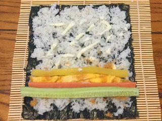 超简单寿司做法,把黄瓜,火腿肠,鸡蛋,调味萝卜平铺在肉松上,从自己这边往外卷
