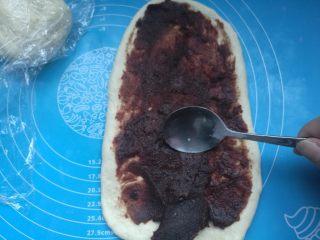 扭扭豆沙小土司,擀成长的椭圆形,机上豆沙馅,用小勺子铺平。