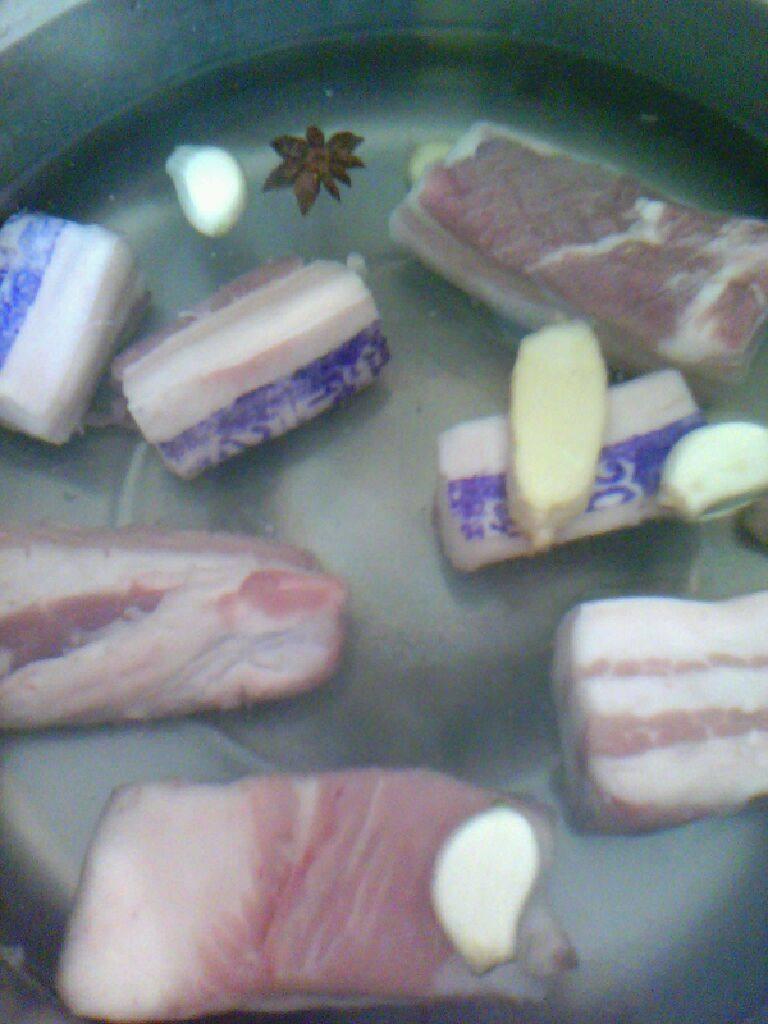 黄蘑扣肉,将五花肉凉水入锅,加入姜,八角,蒜,烧开煮5一l0分钟,将五花肉捞出准用