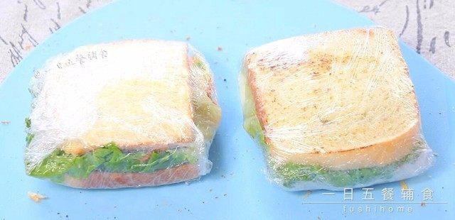 牛油果鸡蛋火腿三明治,将组合好的三明治放在保鲜膜上。卷起来,尽量卷的紧一些。如果是带出门或者第二天吃这样就可以了。