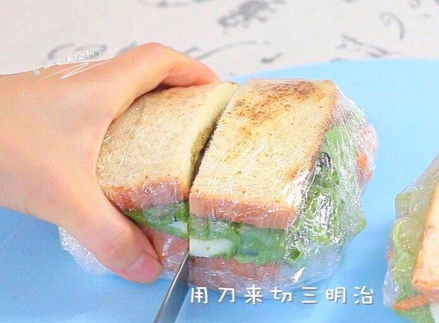 牛油果鸡蛋火腿三明治,准备切了。因为有了保鲜膜切的时候,中间的食物不会掉。吃的时候也很方便!