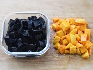 芒果芋圆烧仙草,取出芒果的果肉切小丁块,定型的烧仙草用刀划成小块。