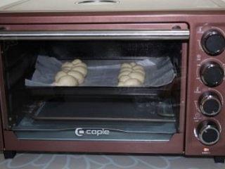 奶香大辫子面包,做好两个麻花辫再摆入烤盘,放入烤箱启动发酵功能继续二次发酵,时间设定40分钟左右