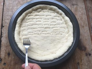 双酱培根披萨,用擀面杖将发酵好的面团擀成跟模具差不多大小的形状,放入模具内,让面团完全贴合四周;用叉子在面团上叉一些小孔,避免面团在烤的时候鼓起来;