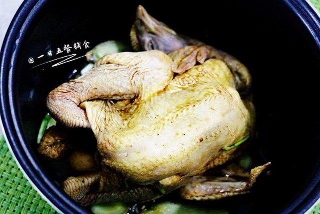 盐焗手撕鸡,把腌制好的三黄鸡放入电饭煲,先脚那面朝天。盖盖。接通电源按下煮饭档。