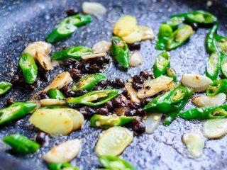 虎皮鹌鹑蛋,放入豆豉、生姜片、蒜片、青椒段小火炒出香辣味。