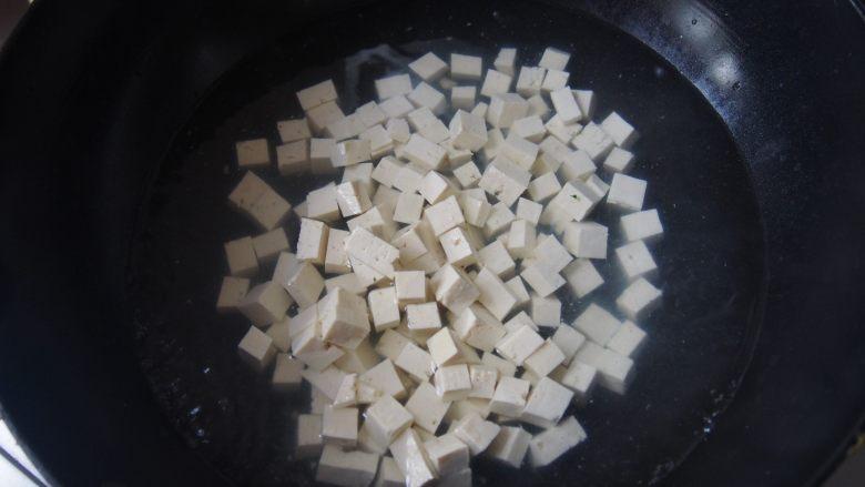 椿芽拌豆腐,锅内放水,水开后放入豆腐,焯水捞出