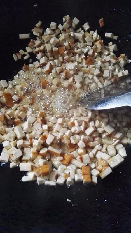 侗家社饭的做法,炒豆腐干,切碎的白色的豆腐干炒到泛黄即可盛出来。