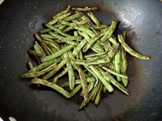 干煸豆角,3.锅中倒入适量的油,油热后将豆角放入锅中,中火开始煸炒。煸炒至豆角表面起皱收缩,呈微黄色时即可捞出。煸好的豆角迅速浸入冰水中