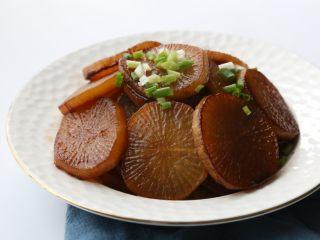 干烧萝卜,最后几分钟调大火力收汁,装盘,撒少许葱花装饰即可。