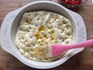 迷迭香佛卡夏,排气排好的面团放入模具中,用手戳一些凹点,刷一层橄榄油,这里的橄榄油我直接用的浸泡小番茄碗里的;