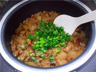 五花肉虾米萝卜焖饭,米饭焖好后响起提示声,打开盖子,倒入蒜叶