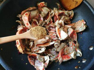吮指香辣螃蟹,放入蟹脚翻炒均匀,加入料酒,生抽,老抽翻炒,舀入一勺香料粉。