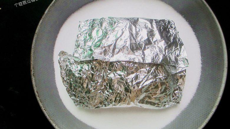 盐焗锡纸金针菇,放入锡纸包,再把余下的盐都倒进锅内,把锡纸包盖住,然后盖上煲盖,用微火慢焗8分钟至熟。