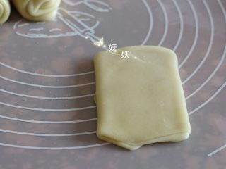 酥掉渣烧饼,翻面,顺形状擀平,呈长方形。