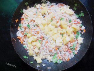 台式凤梨饭,中小火翻炒至米饭散开呈一粒一粒的。放控水后的凤梨果肉丁,翻炒均匀,关火即可食用。