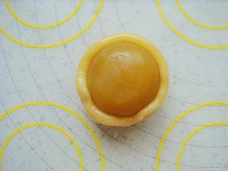 广式莲蓉蛋黄月饼,饼皮按扁放入馅料,同样方法用虎口慢慢上推捏紧收口包好。