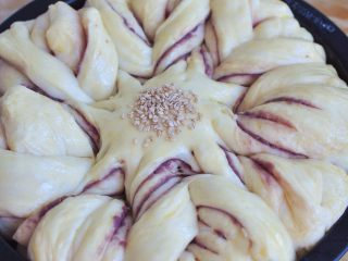 花朵紫薯面包,面团发酵至满模后,表面刷一层蛋液,中间处撒上白芝麻。放入烤箱中,170度烘烤20分钟。