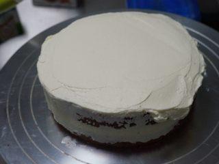 红丝绒奶油奶酪蛋糕,放上第二层,再取部分奶油奶酪霜用抹刀涂抹均匀