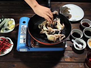 酱烧螃蟹,把蘸有面粉的螃蟹底部放至油锅煎炸1—2分钟 切口定型后,用铲子把螃蟹往锅里面推一下