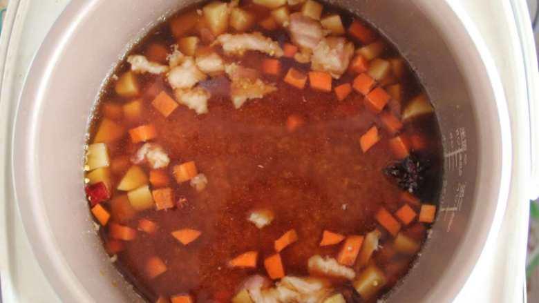 五花肉胡萝卜土豆焖饭,将淘好的米放入电饭煲中,按正常的煮饭键,自动跳后不揭锅多焖10分钟左右即可出锅