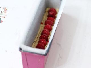 浪漫的的下午茶时光——法式香水磅蛋糕,拌好的面糊装入裱花袋,先将底部铺满,正中位置摆放上覆盆子,不要按压。然后将剩余面糊均匀挤在模具中。最后轻磕震盘,让面糊可以填充满模具。放入预热好的烤箱,中层,165℃烘烤45分钟