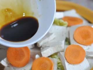 五花肉豆腐锅,生抽、蚝油混合,均匀的淋在菜上。