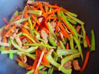 青椒炒肉丁,倒入青椒,翻炒断生加入盐,即可出锅。