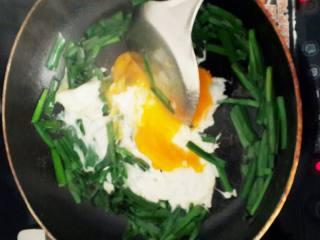 [晨式]阳春面,锅里放少许花生油,开小火,将切断的韭菜放入锅中两下,再打入两个鸡蛋,同时放入盐,味精,少许。动作要快,不然韭菜会烧焦。