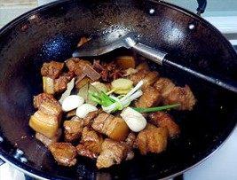 虎皮鹌鹑蛋红烧肉,倒入料酒、生抽、老抽,把准备好的葱姜蒜等香料一起放进去继续翻炒