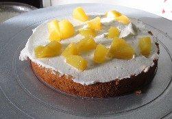 玫瑰奶油蛋糕,取一片蛋糕片放在裱花台上,然后抹上一层奶油。在加上黄桃粒