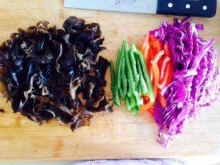黑椒牛柳乌冬面,把紫甘蓝、木耳、彩椒、青椒分别切成丝