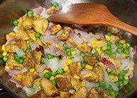 凤梨鸡饭,洋葱切丁先放少许橄榄油煸炒香,倒入豌豆、玉米粒翻炒,再倒入鸡肉混合均匀翻炒,可先加盐进行调味