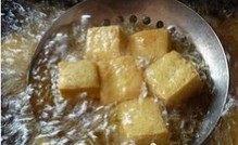 可乐豆腐,炒菜锅里倒入食用油,油热以后将豆腐块放入油中,炸至表面微黄捞出