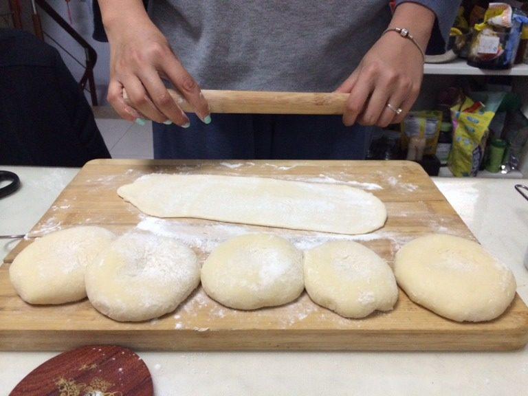 椰蓉吐司,二次揉面结束后,取出面团,面包机不关,面板上撒少许干面粉,将面团分成6份,揉成团,放置10分钟让面团醒一下