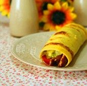 鸡肉卷,鸡蛋饼平铺在盘子上,放入适量的生菜丝、鸡肉和圣女果,卷起翻面放置即可
