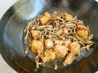 干豆角香焖五花肉,调入适量的生抽、老抽、冰糖、料酒,再加入豆角干翻炒均匀,再加入四汤勺料酒和没过肉块的水