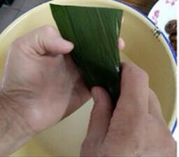 蜜枣花生粽,将粽叶的尾部折过盖起来,左手托好粽子,右手把粽叶尾部对折
