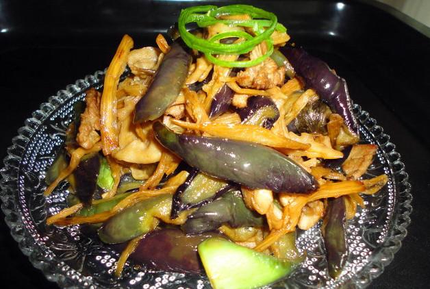 梅干菜烧茄子,锅烧热,放入食用油适量,加入姜末,蒜泥煸炒出香味,茄子入油锅  快速煸炒,放入梅干菜笋干再一同翻炒