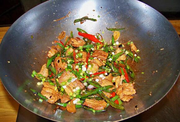 农家小炒肉,下五花肉片,淋生抽、老抽、蒸鱼豉油,翻炒均匀,撒葱花,炒香,起锅即可
