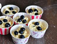 蓝莓麦芬,继续上下翻、压、切,拌匀,将面糊装入模具中,大约7分满,表面撒上几颗蓝莓