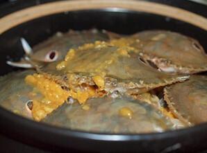 豆酱焗花蟹,淋上大部分的豆酱碎,摆放上蟹壳,将剩余的豆酱碎淋在蟹壳上