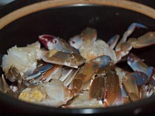 豆酱焗花蟹,油锅下蒜片炒香后放进砂锅,将花蟹摆放在蒜片上
