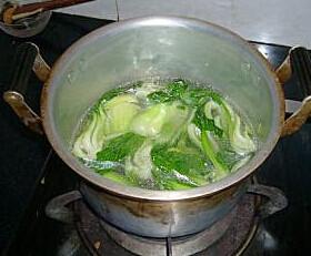腊味煲仔饭 ,另开一锅,放水和适量的盐、油,放青菜去焯熟,然后夹到饭面