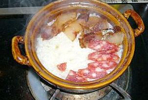 腊味煲仔饭 ,饭放入炉子上煲至只剩下一点点表面的水时放入腊肉、腊肠,小火再焖至表面基本看不到水