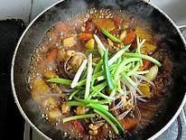 韩式安东炖鸡,加入胡椒粉,放入粉条,放入篙子杆和葱段继续烧制3分钟