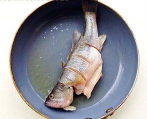 轻松炮制餐厅人气大菜:秘制锡纸包鲈鱼,炒锅加适量油,烧热后,将鱼身拍少许淀粉,放入锅中小火煎